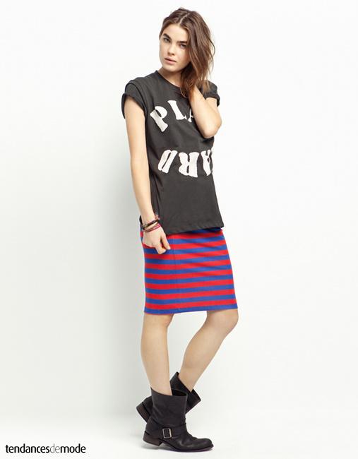 Tee-shirt noir imprimé porté avec une jupe droite rayée bleu et rouge et une paire de boots noires