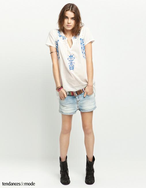 Blouse blanche brodée glissée dans une ceinture péruvienne et un short en jean