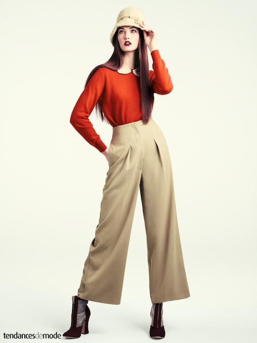 Pantalon beige taille haute surmont� d'un pull orange col Claudine, le tout accessoiris� d'un chapeau cloche r�tro