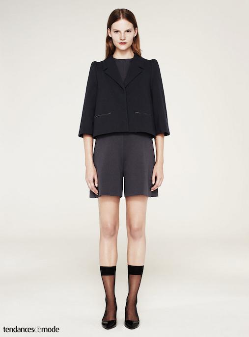 Paletot gris foncé aux manches 3/4 et poches zippées porté avec un combi-short minimaliste