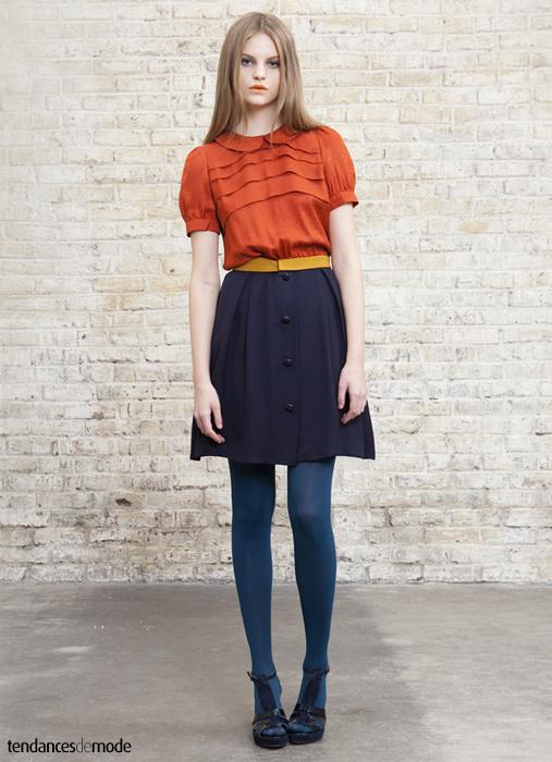 Chemisier orange col Claudine glissé dans une jupe taille haute boutonnée sur le devant