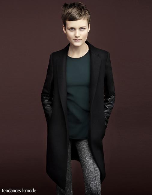 Manteau noir 3/4 à manches en cuir, tee-shirt vert, pantalon gris chiné
