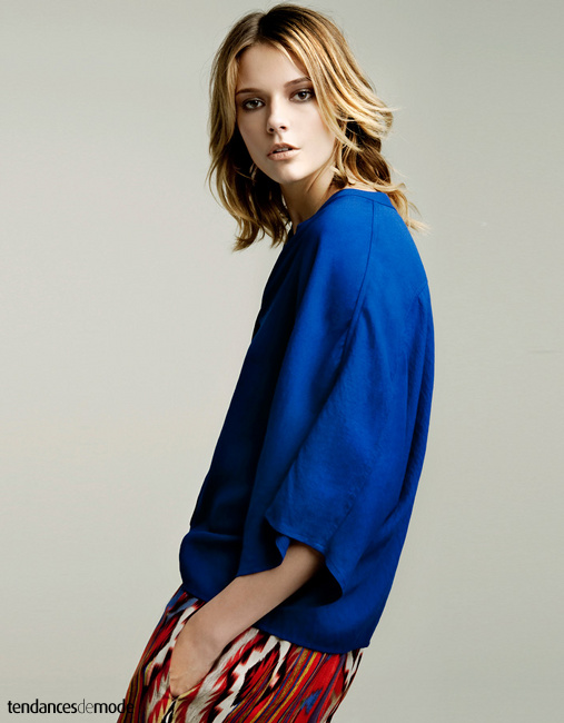 Chemise bleu Klein aux manches raglant portée avec un pantalon Ikat