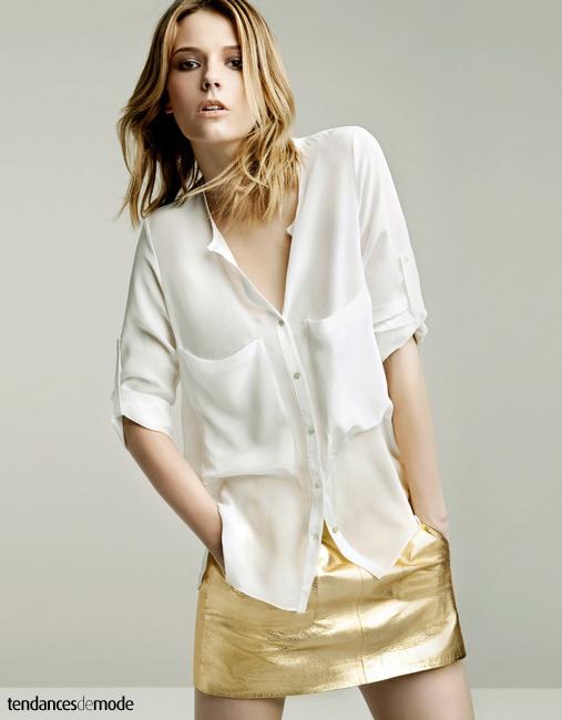 Chemisier blanc en viscose aux poches plaquées porté avec une mini jupe dorée