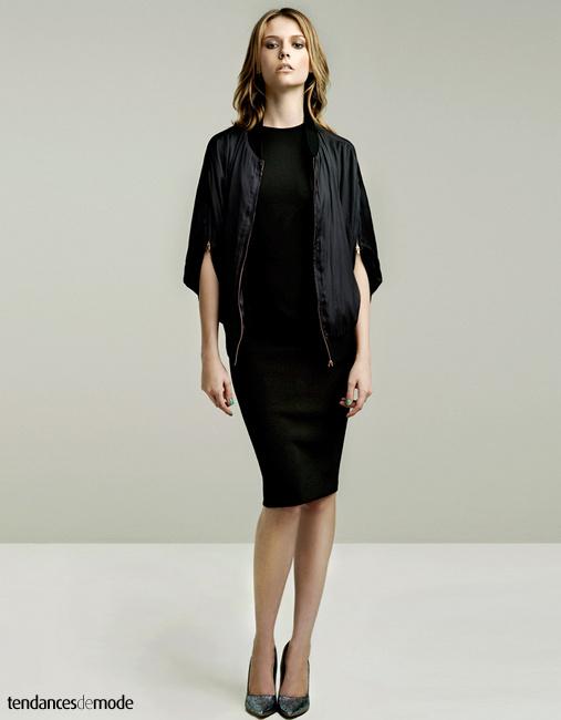 Blouson teddy noir, esprit couture, manches zippées porté avec une robe noire et des escarpins pailletés