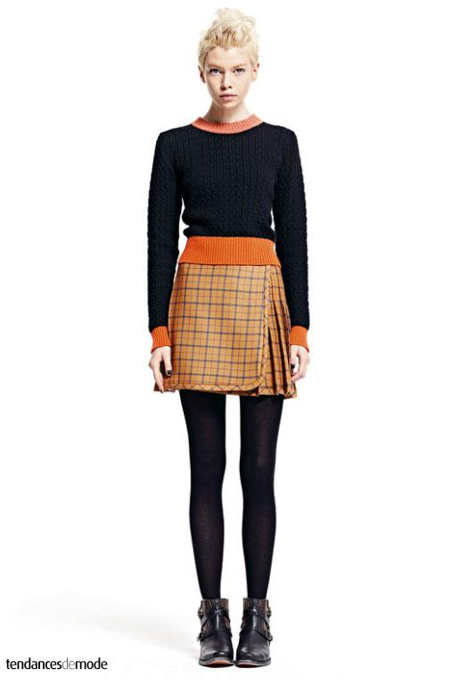 Pull noir torsadé à col contrasté, mini jupe-kilt à carreaux