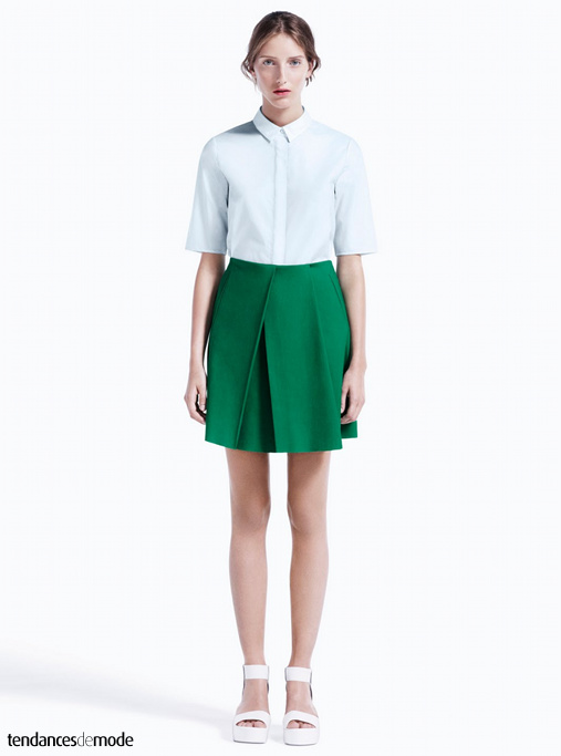 Chemisette blanche, jupe à plis verte et sandales blanches minimalistes