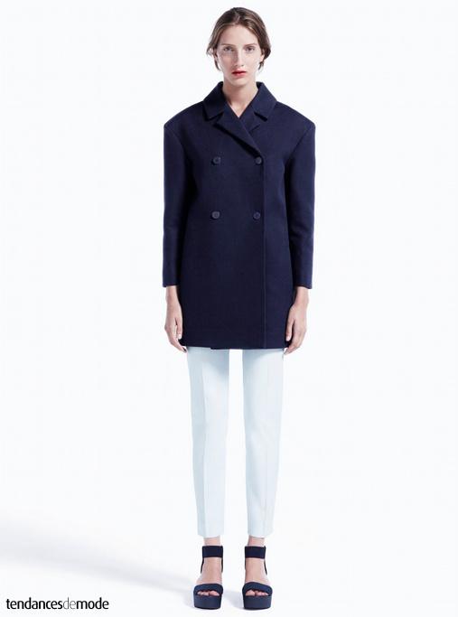 Manteau bleu marine à boutonnages croisés et carrure surdimensionnée, pantalon blanc cigarette et sandales noires minimalistes