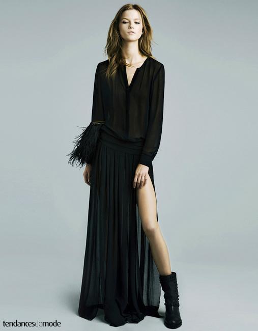 Blouse noire translucide, longue jupe noire plissée et fendue haut sur la cuisse et pochette noire à plumes