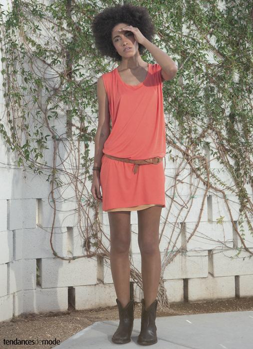 Robe tee-shirt rose superposée à une fine combinaison nude et cintrée par une ceinture en cuir marron