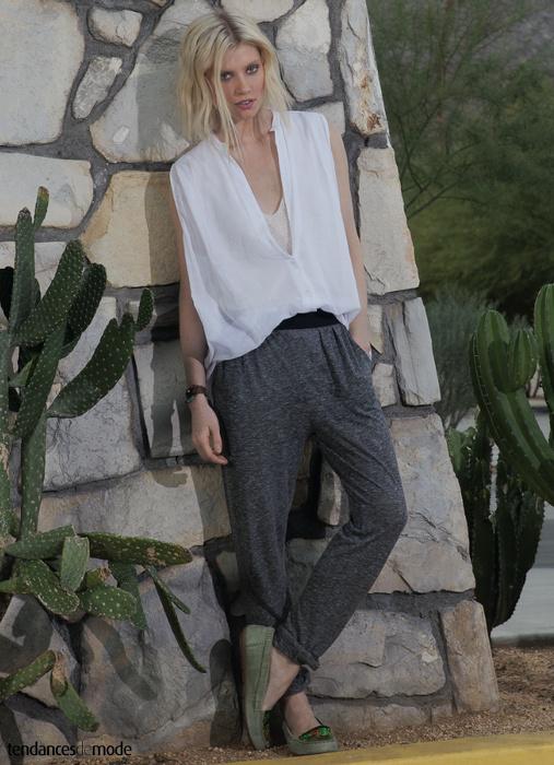 Chemiser blanc, ample et sans manches à demi glissé dans un pantalon de jogging gris chiné